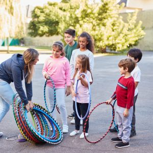 Children in summer camp with sports teacher during physical education with hoops