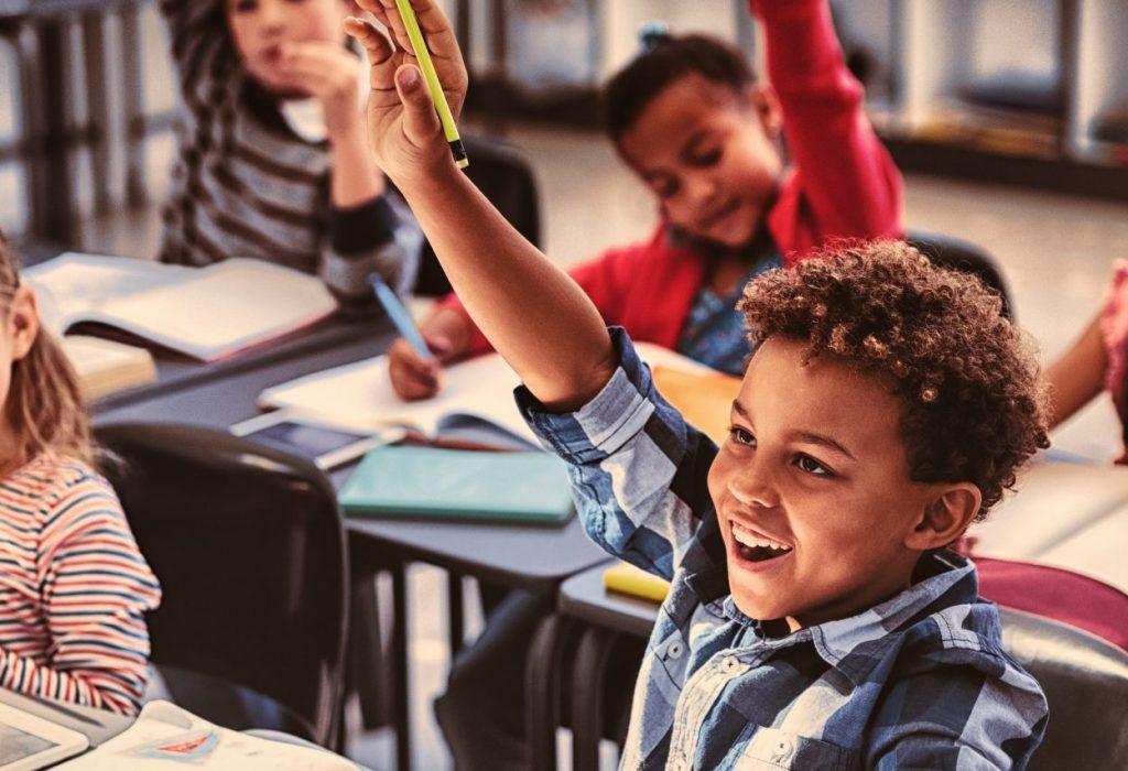 Schoolkids raising their hands in classroom